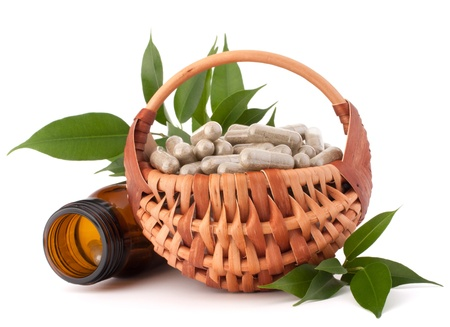 Herbal drug capsules in wicker basket isolated on white background cutout. Alternative medicine concept. photo