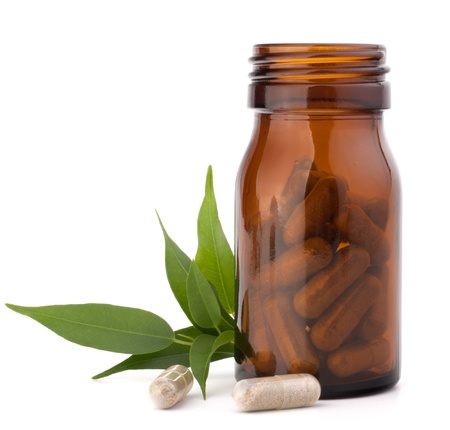 Herbal drug capsules in brown glass bottle isolated on white background cutout. Alternative medicine concept. photo