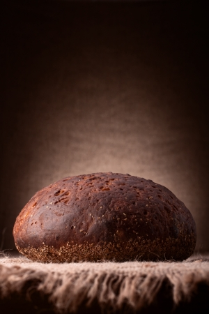 Loaf of rye bread on rustic background photo