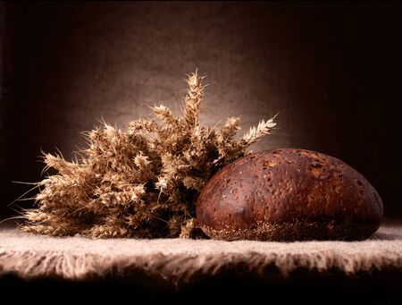 Loaf of bread and rye ears still life on rustic background photo