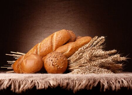 Assortment of breads and ears bunch still life on rustic background photo