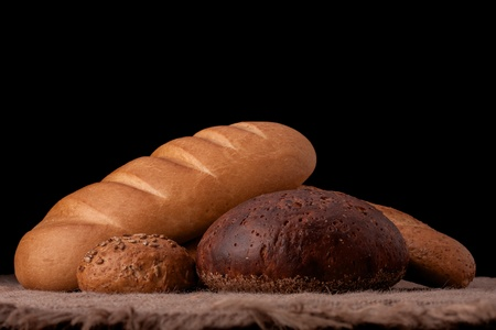 Assortment of breads still life on rustic background photo