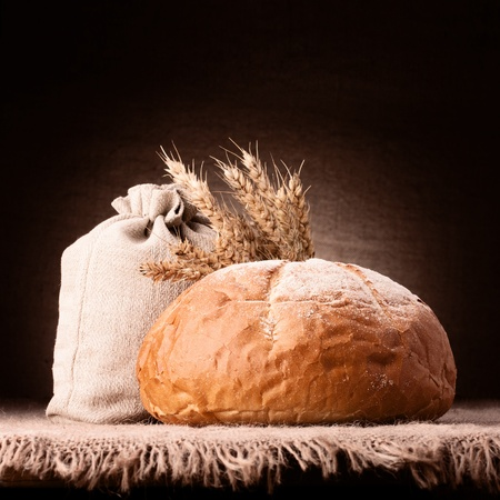 Bread, flour sack and ears bunch still life on rustic background photo