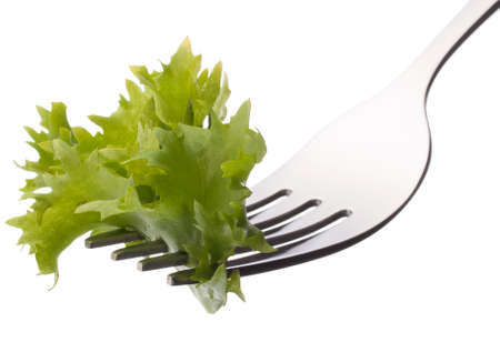 Fresh lettuce salad  on fork isolated on white background cutout. Healthy eating concept. photo