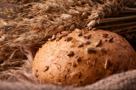 life loaf: Loaf of bread and wheat ears still life on rustic background