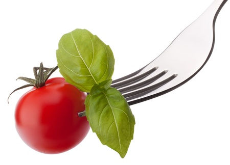 Basil leaf  and cherry tomato on fork isolated on white background cutout. Healthy eating concept. photo