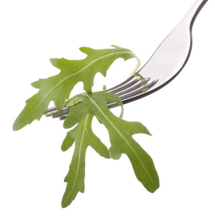 Fresh rucola  salad on fork isolated on white cutout. Healthy eating concept. photo