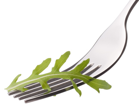 Fresh rucola  salad on fork isolated on white background cutout. Healthy eating concept. photo
