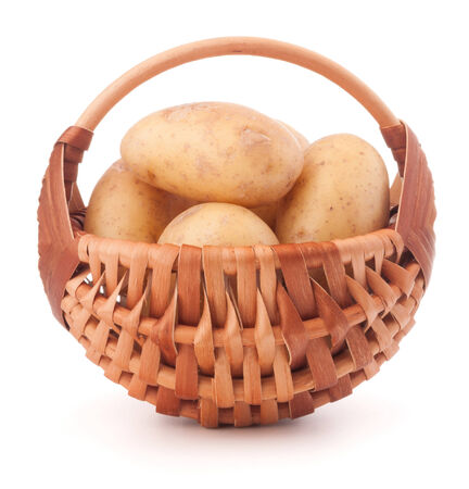 Potato tuber  in wicker basket isolated on white  photo