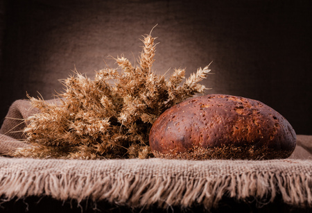 life loaf: Loaf of bread and rye ears still life on rustic background