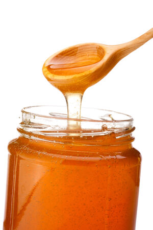 Honey dripping from a wooden honey dipper isolated on white background cutout photo