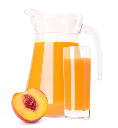 Peach fruit juice in glass jug isolated on white background cutout photo