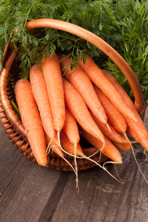 fresh carrots in wicker basket bunch on grungy wooden background photo