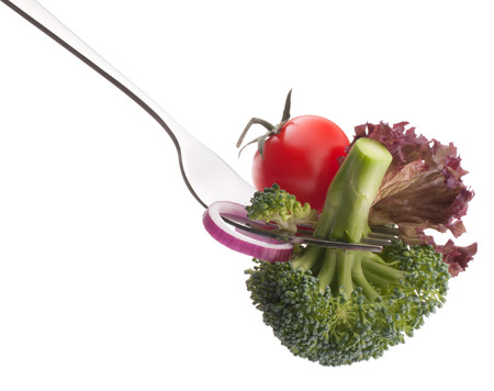 eating utensil: Fresh raw vegetables on fork isolated on white background cutout. Healthy eating concept.