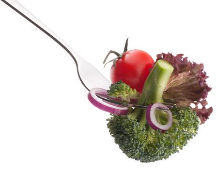 comidas saludables: Verduras crudas frescas en tenedor aisladas sobre fondo blanco