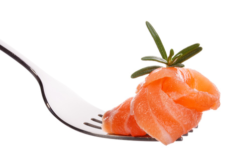 mouthful: Salmon piece on fork isolated on white background