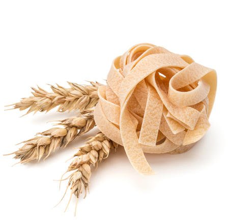 medium group of objects: Italian pasta fettuccine nest and wheat ears still life isolated on white background