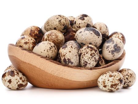 huevos de codorniz en un tazón de madera aislado en el recorte de fondo blanco Foto de archivo