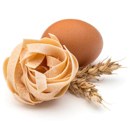 maccheroni: Italian pasta fettuccine nest, egg and wheat ears still life isolated on white background Stock Photo