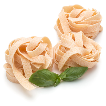 mee: Italian pasta fettuccine nest and basil leaves  isolated on white background cutout Stock Photo