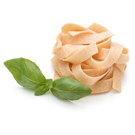 maccheroni: Italian pasta fettuccine nest and basil leaves  isolated on white background cutout Stock Photo