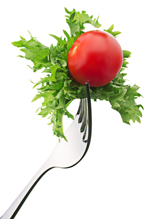 Fresh lettuce salat leaves and cherry tomato on fork isolated on white background cutout. Stock Photo