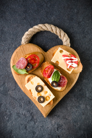 Open faced sandwich canape or crostini on a wooden serving board on dark stone  background closeup. Top view. Stock Photo - 100357014