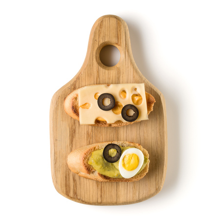 Open faced sandwich canape or crostini on a wooden serving board isolated on white background closeup. Top view. Vegetarian tartarine.