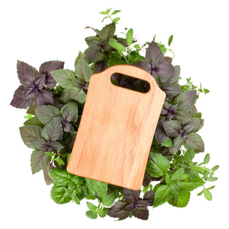 Empty wooden cutting board over various sweet basil herb leaves background. Healthy food concept. Top view with copy space. Stock Photo