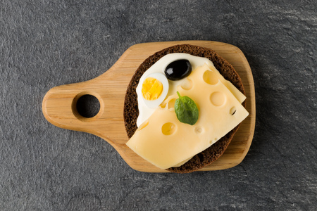 Open  faced cheese sandwich canape or crostini on a wooden serving board  on dark stone background closeup. Top view.