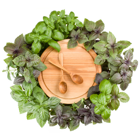 Round wooden cutting board with spoons. Various sweet basil herb leaves edged.. Healthy food concept. Top view. Stock Photo