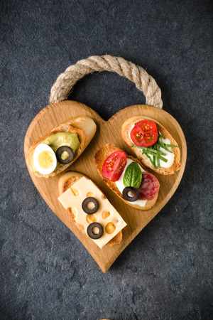 Open faced sandwich canape or crostini on a wooden serving board on dark stone  background closeup. Top view. Stock Photo