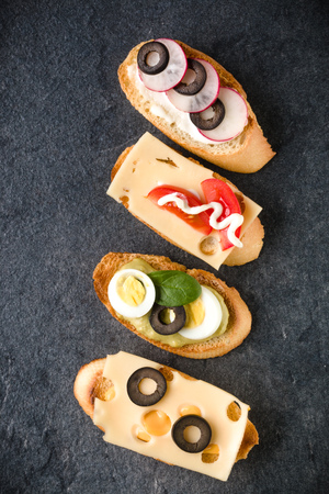 Open faced sandwich canape or crostini on dark stone background closeup. Top view. Stock Photo - 113939773