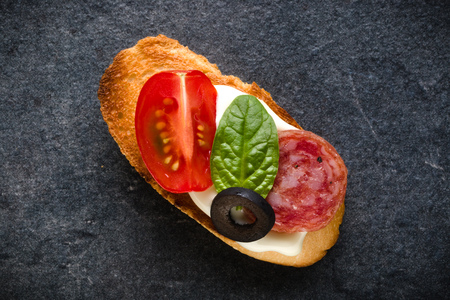 Open faced sandwich canape or crostini on dark stone background closeup. Top view. Stock Photo - 113939819