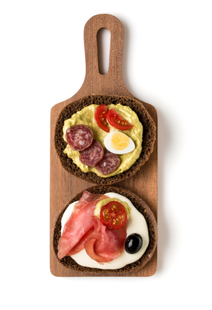 Open  faced sausage sandwich canape or crostini on a wooden serving board  isolated on white background closeup. Top view.