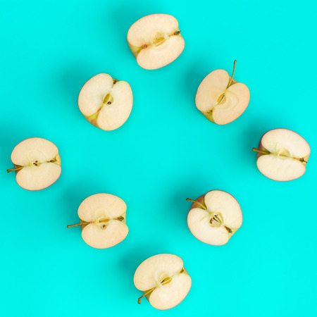 Fruit pattern of apple halves on blue background. Flat lay, top view. Food background.