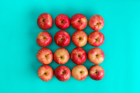 Fruit pattern of red apple on blue background. Flat lay, top view. Pop art design, creative summer concept. Food background.