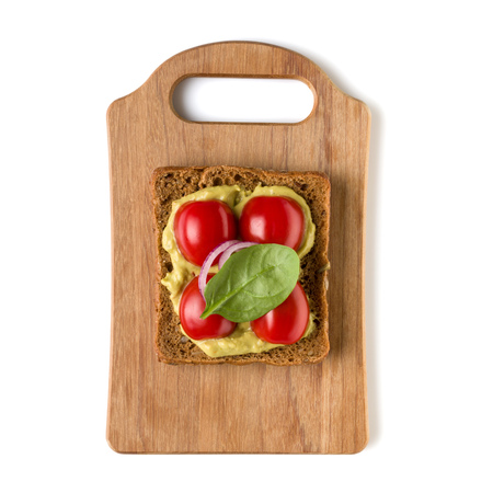 Open  faced vegetable sandwich canape or crostini on a wooden serving board  isolated on white background closeup. Top view.  Vegetarian tartarine. Stock Photo