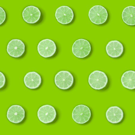 Fruit pattern of lime slices on green background. Flat lay, top view.