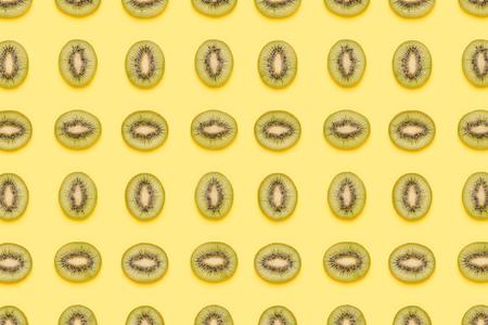 Kiwi slices pattern on green background. Food background. Fruit pattern.  Pop art design, creative summer concept.