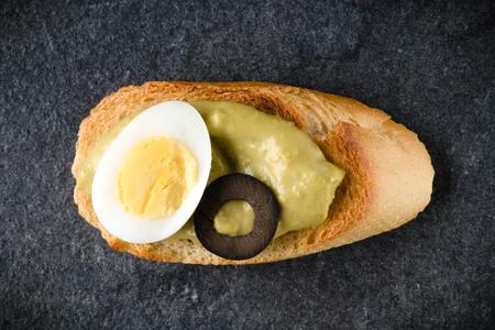 Open faced sandwich canape or crostini on dark stone background closeup. Top view. Vegetarian tartarine.