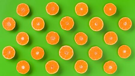 Fruit pattern of fresh orange slices on green background. Flat lay, top view. Pop art design, creative summer concept. Half of citrus in minimal style. 写真素材