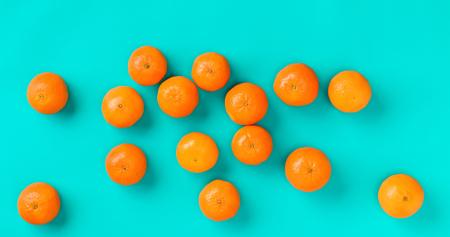 Fruit pattern of fresh mandarin on blue background. Flat lay, top view. Pop art design, creative summer concept. Citrus in minimal style. 写真素材
