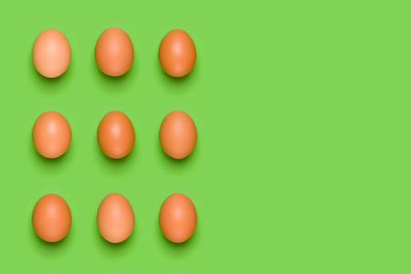 Eggs pattern on green background. Easter concept. Flat lay, top view. Food background. Copy space.