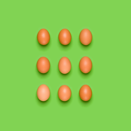 Eggs pattern on green background. Easter concept. Flat lay, top view. Food background.