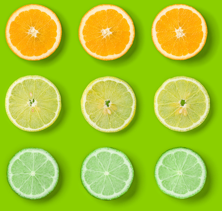 Citrus Fruits pattern on green background. Orange, Lime, Lemon slices background. Flat lay, top view. 写真素材