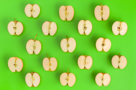 Fruit pattern on green background. Apple halves geometrical layout. Flat lay, top view. Food background.