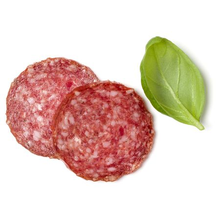 Slices of salami isolated on white background closeup. Sausage and basil leaves top view. Фото со стока