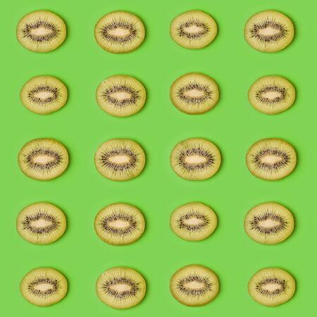 Kiwi slices pattern on green background. Food background. Fruit pattern.  Pop art design, creative summer concept.. Creative layout .