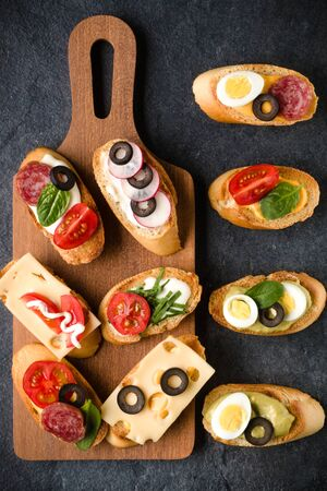 Open faced sandwich canape or crostini on a wooden serving board on dark stone  background closeup. Top view. Banco de Imagens - 130163779